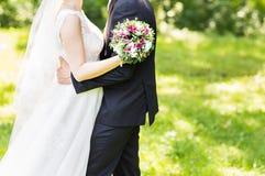 拥抱婚礼的夫妇,拿着花的花束新娘,拥抱她的新郎 图库摄影