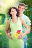 拥抱孕妇的腹部的愉快的人 免版税库存图片