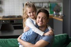 拥抱孩子女儿的愉快的爸爸画象看照相机 免版税库存图片