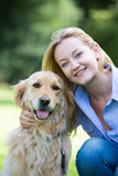 拥抱宠物金毛猎犬的妇女 免版税库存照片