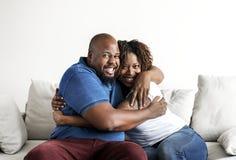 拥抱家庭观念的一对快乐的黑夫妇 库存图片