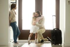 拥抱小女儿的哀伤的父亲在离开长的旅行的前 免版税库存图片
