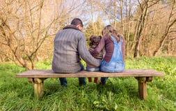 拥抱小女孩的男人和妇女坐a 免版税库存照片