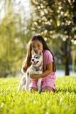 拥抱小狗坐的年轻人的亚洲女孩草 库存图片