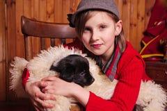 拥抱小狗的女孩包裹在羊皮 农场 图库摄影