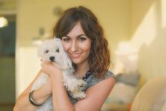 拥抱小白色狗的妇女画象 库存照片