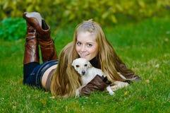 拥抱小的妇女年轻人的美丽的狗 免版税库存图片