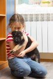 拥抱小的小狗的女孩 图库摄影
