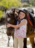 拥抱小的小马马微笑的愉快的佩带的安全骑师盔甲的头美好的美好的女孩7或8岁在夏天 免版税库存照片