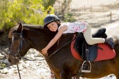 拥抱小马马微笑的愉快的佩带的安全骑师盔甲的甜女孩在暑假 免版税图库摄影