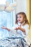 拥抱少许女用连杉衬裤的熊逗人喜爱&# 一个逗人喜爱的婴孩在屋子里坐在窗口在冬天 库存照片