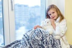 拥抱少许女用连杉衬裤的熊逗人喜爱&# 一个逗人喜爱的婴孩在屋子里坐在窗口在冬天 免版税库存图片