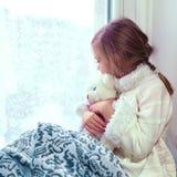 拥抱少许女用连杉衬裤的熊逗人喜爱&# 一个逗人喜爱的婴孩在屋子里坐在窗口在冬天 库存图片