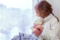 拥抱少许女用连杉衬裤的熊逗人喜爱&# 一个逗人喜爱的婴孩在屋子里坐在窗口在冬天 免版税库存照片