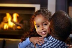拥抱少许微笑的非洲的美丽的父亲女孩 免版税库存图片
