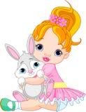 拥抱少许玩具的兔宝宝女孩 免版税库存图片