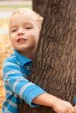 拥抱少许结构树的男孩 免版税库存图片