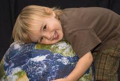 拥抱少许行星的男孩 免版税库存照片