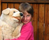 拥抱少许长毛绒玩具的大狗女孩 免版税库存图片