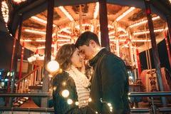 拥抱年轻的夫妇亲吻和室外在夜街道在圣诞节时间 免版税库存图片
