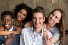 拥抱微笑的多种族夫妇对照相机,摆在为pictur 免版税库存图片