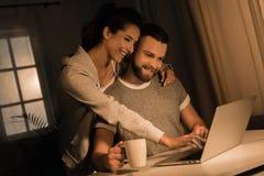 拥抱微笑的夫妇,当在家时使用膝上型计算机 库存图片