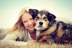 拥抱德国牧羊犬狗的微笑的妇女 库存照片