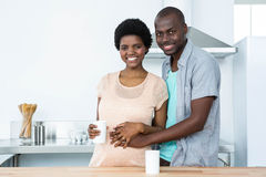 拥抱怀孕的夫妇,当食用咖啡时 免版税库存图片
