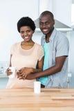 拥抱怀孕的夫妇,当食用咖啡时 免版税库存照片