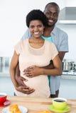拥抱怀孕的夫妇,当食用早餐时 免版税库存图片