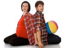 拥抱怀孕的妈妈的家庭 免版税库存照片