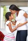 拥抱怀孕的母亲的女儿 免版税库存图片