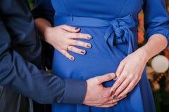 拥抱怀孕的腹部人的手 免版税库存图片