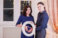拥抱怀孕的腹部人的手 库存图片