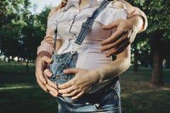 拥抱怀孕的腹部的母亲和父亲手 免版税库存图片