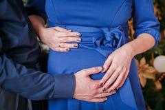 拥抱怀孕的腹部 免版税图库摄影