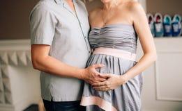 拥抱怀孕的妻子的丈夫 一个人的手妇女`的s鼓起 库存照片