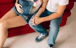拥抱怀孕的妻子的丈夫 一个人的手妇女`的s鼓起 免版税库存照片