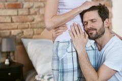 拥抱怀孕的妻子的愉快的人 免版税库存照片