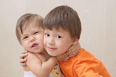 拥抱愉快微笑的兄弟和姐妹 免版税库存照片