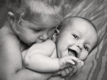拥抱愉快的小女孩亲吻兄弟 免版税库存照片