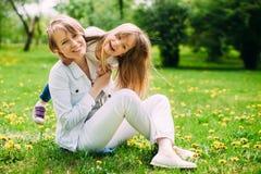 拥抱愉快的母亲和女儿步行的在公园绿色草坪的 免版税库存图片