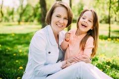 拥抱愉快的母亲和女儿步行的在公园绿色草坪的 免版税库存照片
