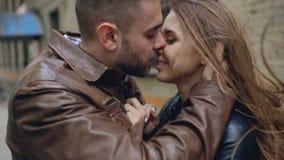 拥抱愉快的爱恋的夫妇特写镜头亲吻和,当在城市街道时的havinhg步行 免版税库存图片