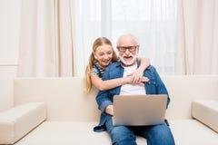 拥抱愉快的祖父的小女孩在家使用膝上型计算机 免版税库存照片