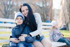 拥抱或拿着儿子年轻男孩,坐的孤独的一个小女孩的愉快的微笑的&看的照相机美丽的母亲 免版税库存图片
