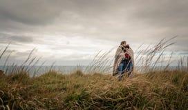 拥抱户外在a的毯子下的年轻夫妇 库存照片
