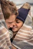 拥抱户外在a的毯子下的年轻夫妇 免版税图库摄影