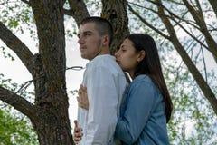 拥抱户外晴朗的夏日的年轻美丽的男人和妇女夫妇  免版税库存照片
