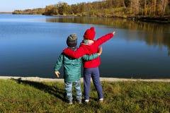 拥抱户外的男孩和女孩 愉快儿童享用室外 兄弟和姐妹走 免版税库存照片